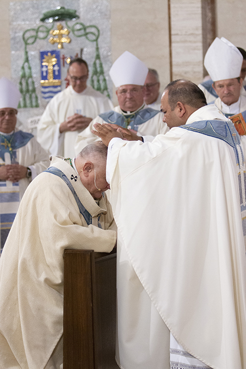 Father Martin Muñoz gives his first blessing to Archbishop Thomas Wenski at the conclusion of the ordination Mass.
