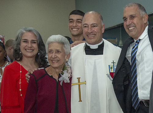 Father Elkin Sierra takes a break from giving out blessings to pose with his family, from left: his sister, Ana, his mother, Stella, one of his nephews, Vincent, 18, and his brother, Luis, who also became a firefighter/paramedic.