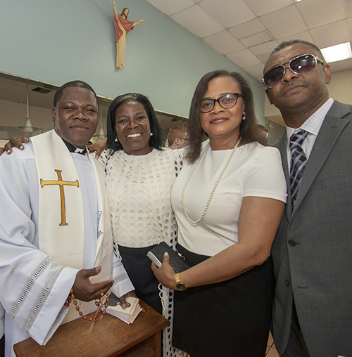 While giving out blessings, newly ordained Father Reynold Brevil poses with Ketty Descardes, second from right, the woman