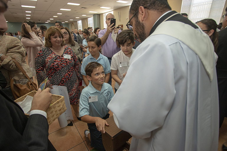Newly ordained Father Jose Enrique Lopez blesses a fifth-grader from St. Bonaventure School in Davie. The fifth grade class