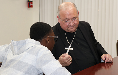 Miami Auxiliary Bishop Peter Baldacchino shows his pectoral cross to Bryan Williamson, a student reporter from St. James School in North Miami, who sat in on the press conference at the Pastoral Center May 16, a day after the Vatican announced the bishop's appointment to the Diocese of Las Cruces, New Mexico.
