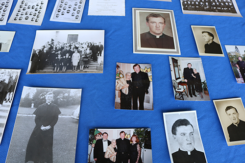 Photos of Father Thomas Foudy are displayed as part of a memorial to him May 19, the day he died. The photos were found at the parish days before his death when staff were looking for historical items to display for the parish's 60th anniversary celebration planned for the same day he died. The man who served the parish from 1989 to 2015 was loved by many and helped expand and grow the parish and school in many initiatives.