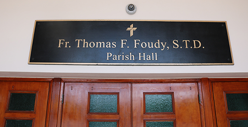 A plaque over the door of the St. Coleman Parish Hall features the name of Father Thomas F. Foudy, who died May 19, hours before the parish gathered to mark its 60th anniversary. The day turned into a celebration of Father Foudy's life. According to those close to him, Father Foudy, former pastor, loved St. Coleman Parish and School and was dedicated to Catholic education, supporting and helping with various initiatives to expand facilities and opportunities for students. The parish and school dedicated the parish hall to him as a permanent tribute.