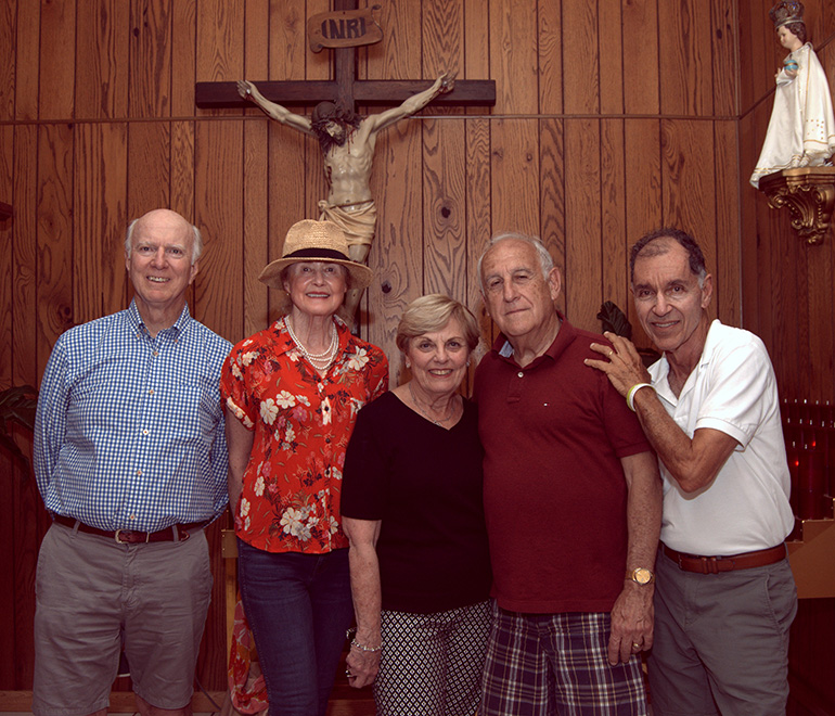 Alumni of Sts. Peter and Paul School revisit the parent church in Miami during their 70th anniversary reunion. They're standing in the chapel, where the church's original crucifix stands. From left are Joe Annis, Barbara Annis, Nancy Kelly Dodd, Dr. Serge Martinez and Paul George.