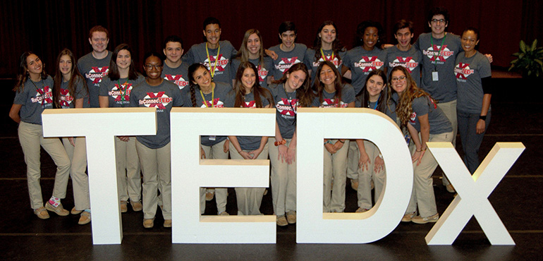 Students group behind the logo of TEDx, a forum of speeches and performances they helped to produce at St. Thomas Aquinas High School in Fort Lauderdale.