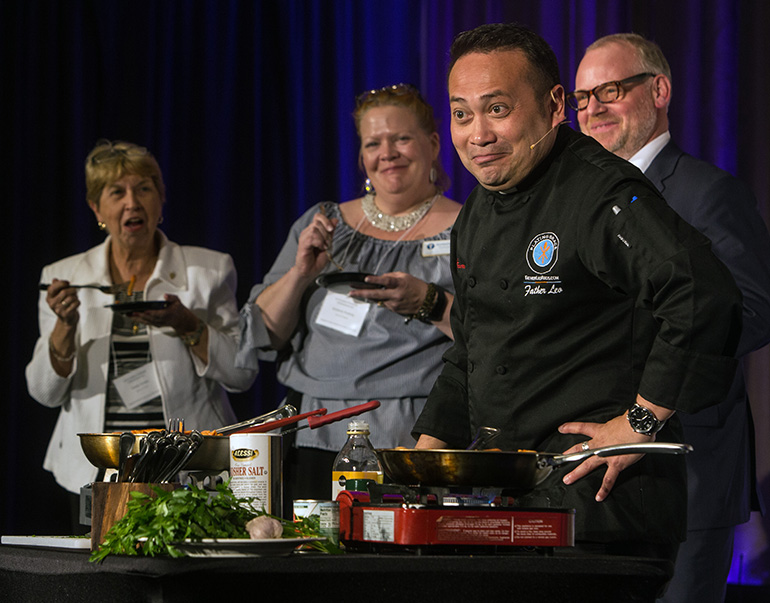 Audience members enjoy Father Leo Patalinghug's just-made penne alla vodka during the Second Statewide Stewardship Day, held at the Hilton Hotel in downtown Miami May 4. The priest founded Plating Grace, a movement to bring families back to the dinner table. His most recent book is