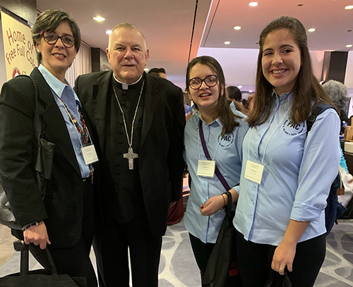 From left, Sara Salomon and her daughters, Mara and Lara Briceño, pose with Archbishop Thomas Wenski after he celebrated the opening Mass at the Second Statewide Stewardship Day, held at the Hilton Hotel in downtown Miami May 4. The family is involved with the Por Amor a Cristo (For the love of Christ) stewardship group at at their parish, St. Dominic Church, Miami.