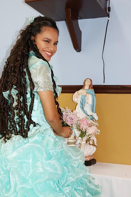 Itzamar Cortes sonríe al colocarle un ramo de rosas a la imagen de la Virgen María después de su consagración a ella, como parte de la Misa por sus 15 años.