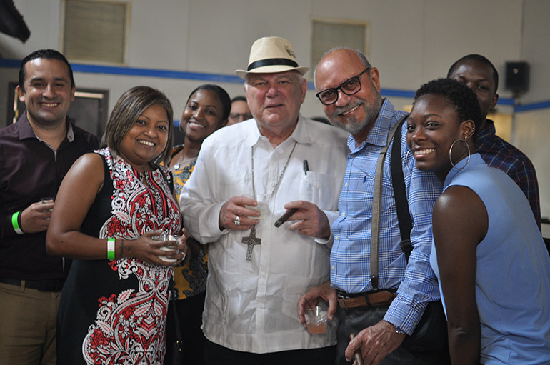 Dressed for the occasion, Archbishop Thomas Wenski takes a picture with Catholic Charities staff during the annual Havana Nights fundraiser for its Unaccompanied Minors Program.