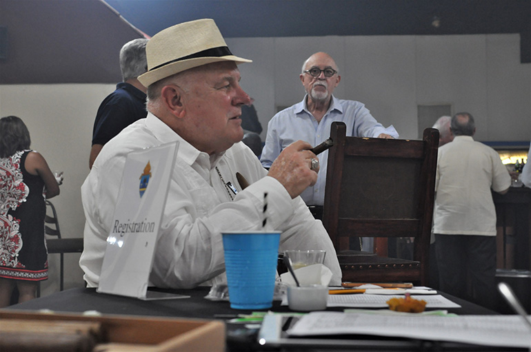 Archbishop Thomas Wenski relaxes with a cigar near the sign-in table for the annual Havana Nights fundraiser for Catholic Charities' Unaccompanied Minors Program.