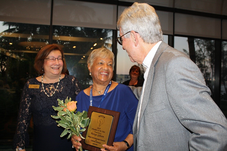 The Miami Archdiocesan Council of Catholic Women's Outstanding Member of the Year, Bettye Gibson of the Cathedral Council of Catholic Women, joyfully accepts her award from MACCW President Lisa Shelly and Father Michael J. Greer, the group's spiritual advisor, during the MACCW 61st annual convention at the Miami Airport Hilton May 17.