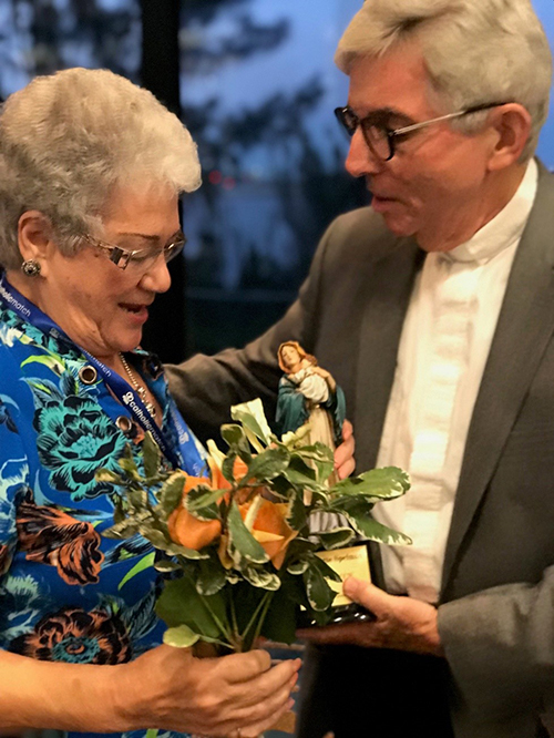 The Miami Archdiocesan Council of Catholic Women's Our Lady of Good Counsel award recipient, Claudette Spelman, of St. Andrew Council, accepts a statue of the group's namesake presented to her by Father Michael J. Greer, spiritual advisor, during the MACCW's 61st annual convention at the Miami Airport Hilton May 17.