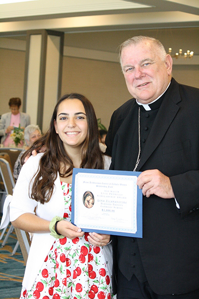 Archbishop Thomas Wenski poses with Blessed Trinity eighth-grade student Gena Escanaverino, one of three scholarship recipients awarded $ 5,000 to attend a Catholic high school. The award was presented at the Miami Archdiocesan Council of Catholic Women's Scholarship Award Luncheon, held during the group's 61st annual convention, May 18 at the Miami Airport Hilton.