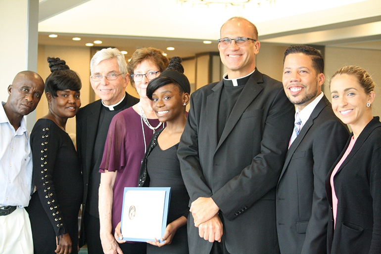 Scholarship Award recipient Christy Ramonvil, from St. Mary Cathedral School, poses with, from left, her stepfather, Pascal Phanor, her mother Ketelie St. Bert, Father Michael J. Greer, the Miami Archdiocesan Council of Catholic Women's spiritual advisor, Mary Weber, MACCW Scholarship Award coordinator, Father Christopher Marino, rector of St. Mary Cathedral, Edwardo Flor, cathedral school principal, and Katrina DeLaFe, assistant principal.