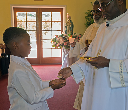 Jaron Johnson, Jr., 8, receives his first Communion from Father Fidelis Nwankwo as Deacon Thomas Dawson looks on. His first Communion coincided with the 65th anniversary of St. Philip Neri Church, May 26, 2019.