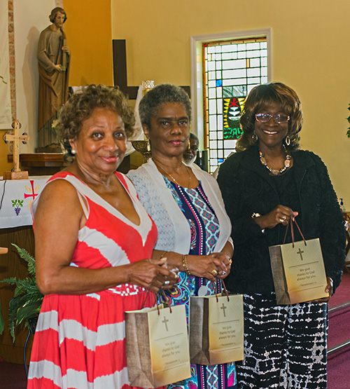 From left, Teresa Davis, Andrea Patterson and Constance Thornton hold the gifts given to them for their service to St. Philp Neri Church on the day the parish celebrated its 65th anniversary, May 26, 2019.
