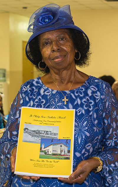 Lona B. Matthews holds the 47-page St. Philip Neri history booklet which she put together.