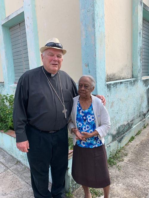 El arzobispo Thomas Wenski saluda a una mujer de 103 años durante una visita a un asilo de ancianos administrado por la Iglesia Católica junto a la iglesia de San Francisco de Paula en La Víbora, un barrio en las afueras de La Habana, 27 de mayo de 2019.