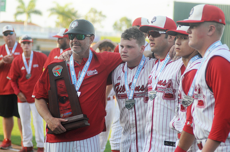 Cardinal Gibbons head coach Jason Hamilton, left, holds the runner-up trophy with seniors Kevin Hirsch, John Diaz, Kyle Kuramoto and Keanu Buerosse following the Chiefs' 6-3 eight-inning loss to Melbourne Central Catholic in the Class 5A baseball state championship game at Hammond Stadium in Fort Myers.