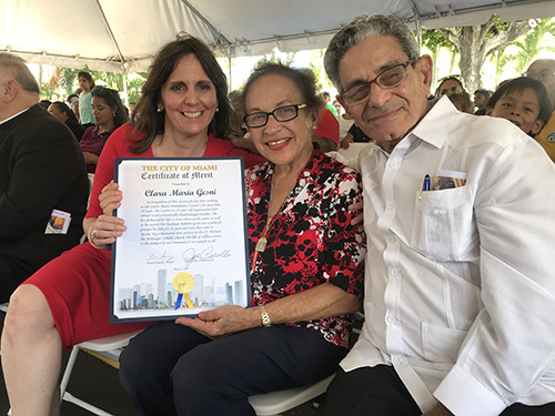 Madelyn R. Llanes, left, program director of Centro Mater East I and II, poses with veteran teacher Clara Gesni and her husband, Roberto, and the Certificate of Merit she received from the City of Miami upon her upcoming retirement.