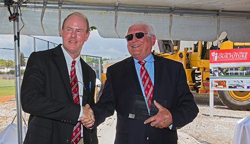 Thomas Mahon, left, incoming president at Cardinal Gibbons High, and Paul Ott, a 1966 graduate and outgoing principal, shake hands at the blessing and groundbreaking ceremony for the school's new STEAM center.