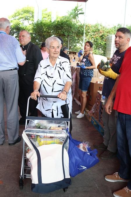 Evangelina Díaz con su carrito lleno de alimentos que recibió el 8 de junio, en el nuevo local del banco de comida de la Sociedad San Vicente de Paúl, de la parroquia Mother of Christ. Detrás, el Arzobispo Thomas Wenski habla con Jim Werle, tesorero del concilio arquidiocesano de la Sociedad San Vicente de Paúl.
