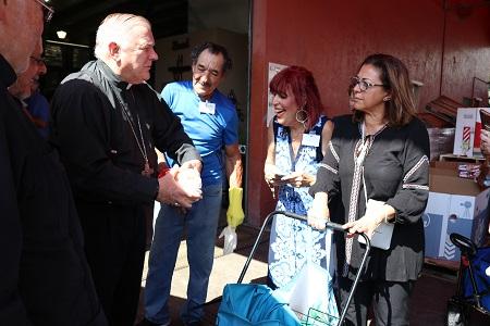 El Arzobispo Thomas Wenski le entrega un pollo entero a María Melián, durante su visita al nuevo local del banco de comida de la Sociedad San Vicente de Paul de la parroquia Mother of Christ, el 8 de junio.