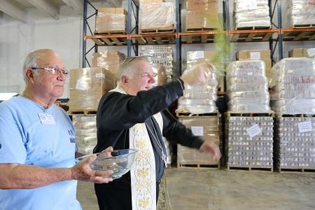 El Arzobispo Thomas Wenski bendice el nuevo local del banco de comida de la Sociedad San Vicente de Paul, en la parroquia Mother of Christ, al sur del aeropuerto Tamiani, en Kendall, el 8 de junio. Le lleva el agua bendita, el voluntario de San Vicente, Enrique Ariza.