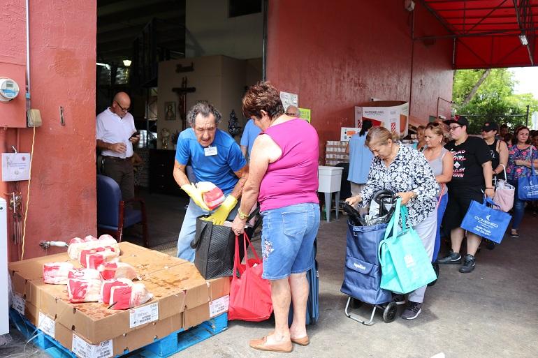 Cientos de surfloridanos reciben comida gratis de la Sociedad de San Vicente de Paul, el 8 de junio, en el nuevo local del banco de comida de la parroquia Mother of Christ, en Kendall, al sur del aeropuerto Tamiami.