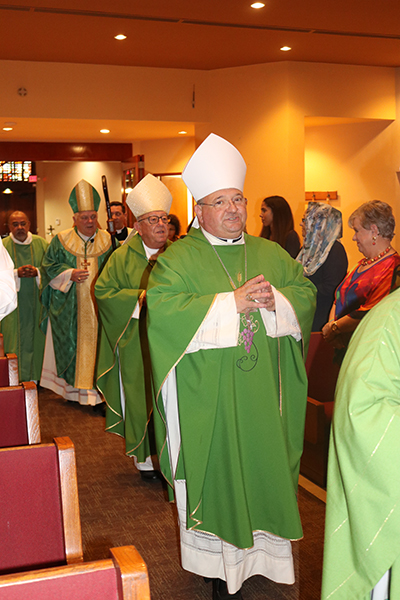 Auxiliary Bishop Peter Baldacchino processes into St. Martha Church for the farewell Mass celebrated at the Pastoral Center June 14. Entering with him are Archbishop Emeritus John Favalora and Archbishop Thomas Wenski.