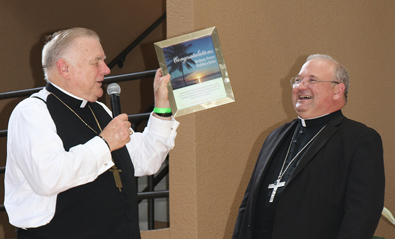 Archbishop Thomas Wenski presents Auxiliary Bishop Peter Baldacchino with a framed version of a congratulatory ad purchased by the Archdiocese of Miami for Agua Viva, the newspaper of the Diocese of Las Cruces, New Mexico. The photo, taken by Sister Elizabeth Worley, a Sister of St. Joseph who serves as archdiocesan chancellor for administration, is a sunset view of the bay close to St. Kieran Church, Miami, where Bishop Baldacchino served as pastor for five years.