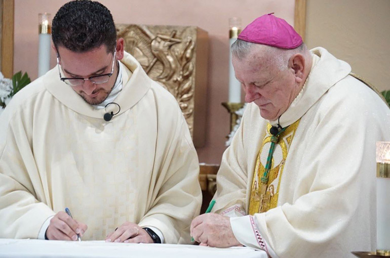 Archbishop Thomas Wenski and Father Bryan Garcia sign the papers officially naming him pastor, rather than administrator, of St. Bernadette Parish in Hollywood, June 15, 2019.