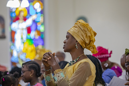 A member of the Archdiocese of Miami's Nigerian Apostolate prays during the Mass celebrating 25 years of the apostolate's establishment, June 16, 2019 at St. Monica Church, Miami Gardens.