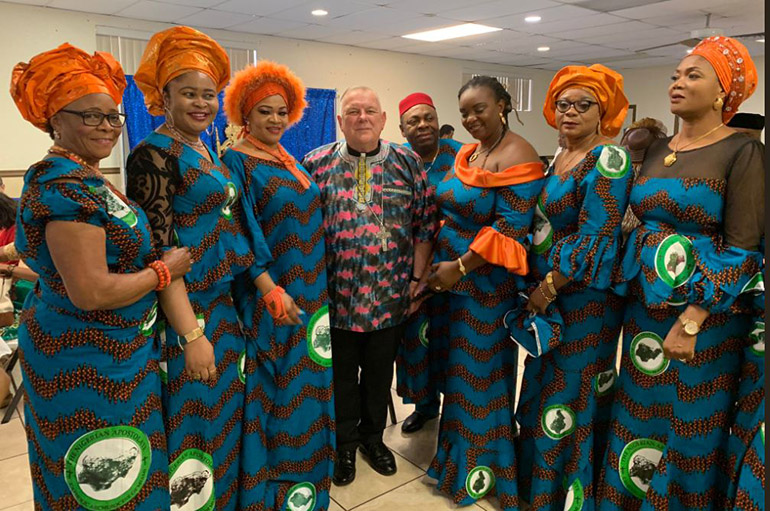 Wearing traditional garb, Archbishop Thomas Wenski poses with some of the members of the Nigerian Apostolate here after the Mass to mark its 25th anniversary in the archdiocese, June 16, 2019.