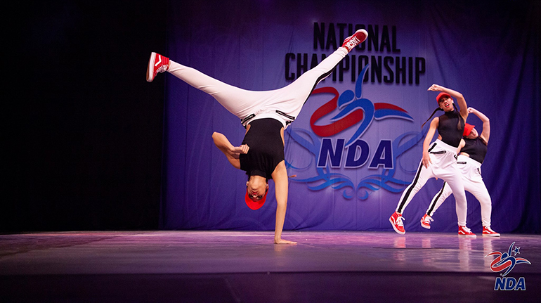 Archbishop McCarthy High School's Madison Rojas does a trick as Marcela Atehortua and Amber Romero move in the background during the Jazz competition at the National Dance Alliance's National Championship in Orlando in February.