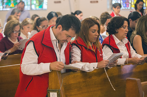Fabrizio and Monica Acquaviva, of Mission for the Love of God Worldwide, pray the rosary before the Mass where Archbishop Thomas Wenski consecrated the Village of Key Biscayne to the Sacred Hearts of Jesus and Mary.