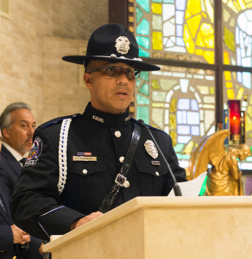 Key Biscayne Honor Guard member, Officer Frank Carvajal, reads one of the Prayers of the Faithful during the Mass of consecration for the Village of Key Biscayne.