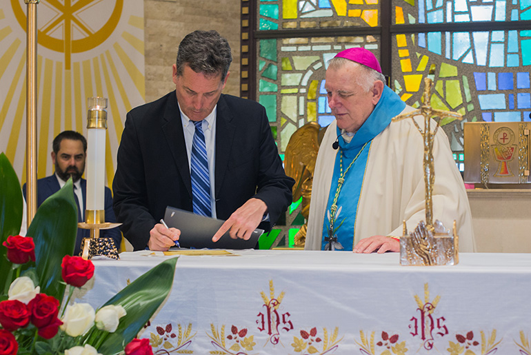Archbishop Thomas Wenski looks on as Key Biscayne Mayor Michael Davey signs the consecration document for the village.