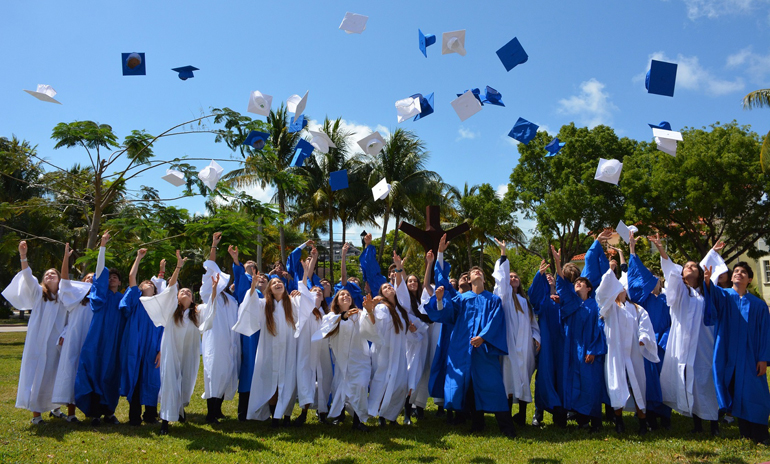 Eighth grade students from St. Agnes Academy throw their caps up in graduation celebration.