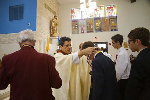 Father Juan Carlos Paguaga presents a student-athlete with a medal during the All Catholic Conference All Star Mass held at St. Agnes Church in Key Biscayne on May 5.