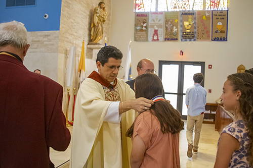 Father Juan Carlos Paguaga presents Gena Escanaverino, from Blessed Trinity School in Virginia Gardens, with a medal during the All Catholic Conference All Star Mass held at St. Agnes Church in Key Biscayne on May 5.