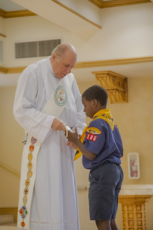 Bryce Griffiths, Cub Scout from St. Bartholomew Church, Miramar, receives the Light of Christ emblem from Deacon Emilio Blanco during the Archdiocese of Miami's Catholic Scouting Presentation Mass.