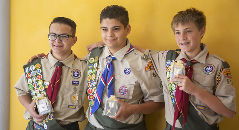 From left, Sebastian Gomez, Anthony Arteta and Zachary Seymour show the emblems they received at the Archdiocese of Miami's Catholic Scouting Presentation Mass.