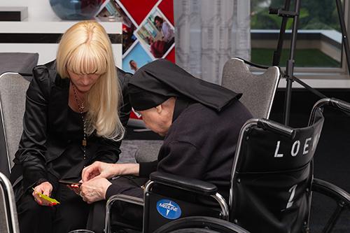 Precious Blood Sister Philip Marie Burle, spiritual director and retreat facilitator, prays for  Katalin Filtranti during the 56th annual Maronite convention held in Miami Beach, June 26-30.