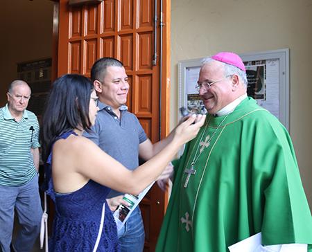 Newlyweds Daniel Torres and Andrea Romero greet Bishop Peter Baldacchino after Sunday Mass on June 30 at St. Kieran Parish.