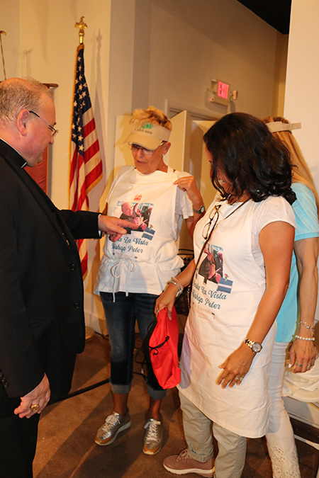 """Pat Tetcash, a parishioner of St. Kieran, shows Bishop Peter Baldacchino an apron they made to raise funds for the new Diocese the Bishop was assigned, Las Cruces. The apron has a photograph of the bishop and the message """"Hasta la vista Bishop Peter"""". With them another parishioner, Jenny Garcia."""