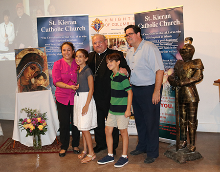 Bishop Peter Baldacchino poses with the Botero family, parishioners of St. Kieran. Left, Claudia (mother) and Alexandra. Right, Julian and Thomas (the father). The Botero family returned to the Church after hearing a homily from Bishop Baldacchino inviting them to return no matter what had happened.