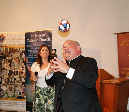 Bishop Peter Baldacchino plays with a small soccer ball given to him by a parishioner from St. Kieran during the farewell celebration.