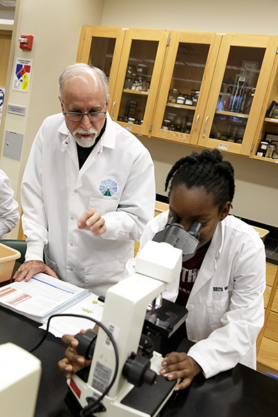 Father Alfred Cioffi helps students conduct biology experiments during a lab class at St. Thomas University in 2016.