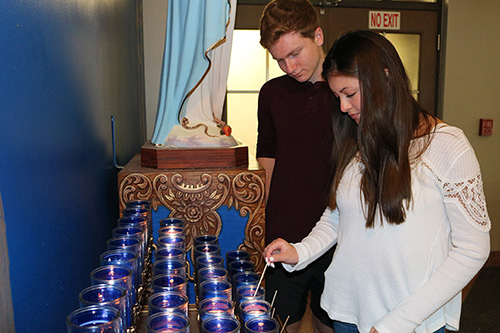 Alexa Reed, 16, and her cousin Joshua Reed, 18, light candles for the souls killed at Marjory Stoneman Douglas High School on the one-year anniversary of the tragic event. They attended a holy hour at Mary Help of Christians in Parkland held to pray for the victims and the families and for peace.